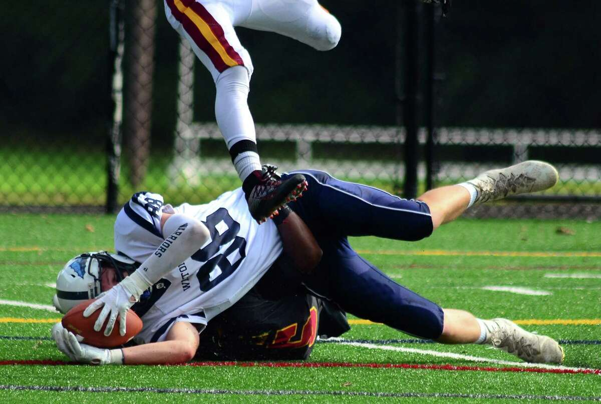 Wilton's Michael Coffey is tackled by St. Joseph's Davee Silas during high school football action in Trumbull, Conn., on Saturday Sept. 29, 2018.