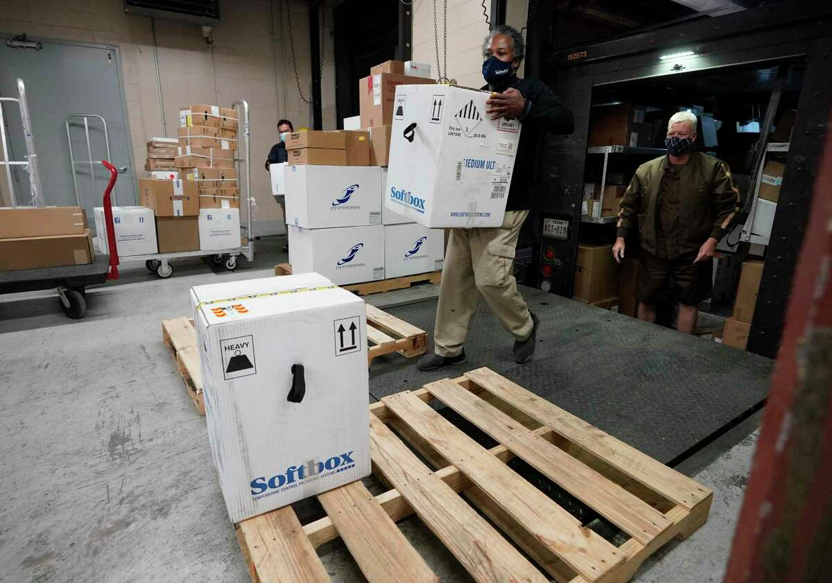 Kevin Anderson, loading dock coordinator at Houston Methodist Hospital, left, carries a box of COVID-19 vaccines after they arrived by UPS Tuesday, Dec. 15, 2020 in Houston. The hospital received their first shipment this morning and will begin administering the vaccine today.