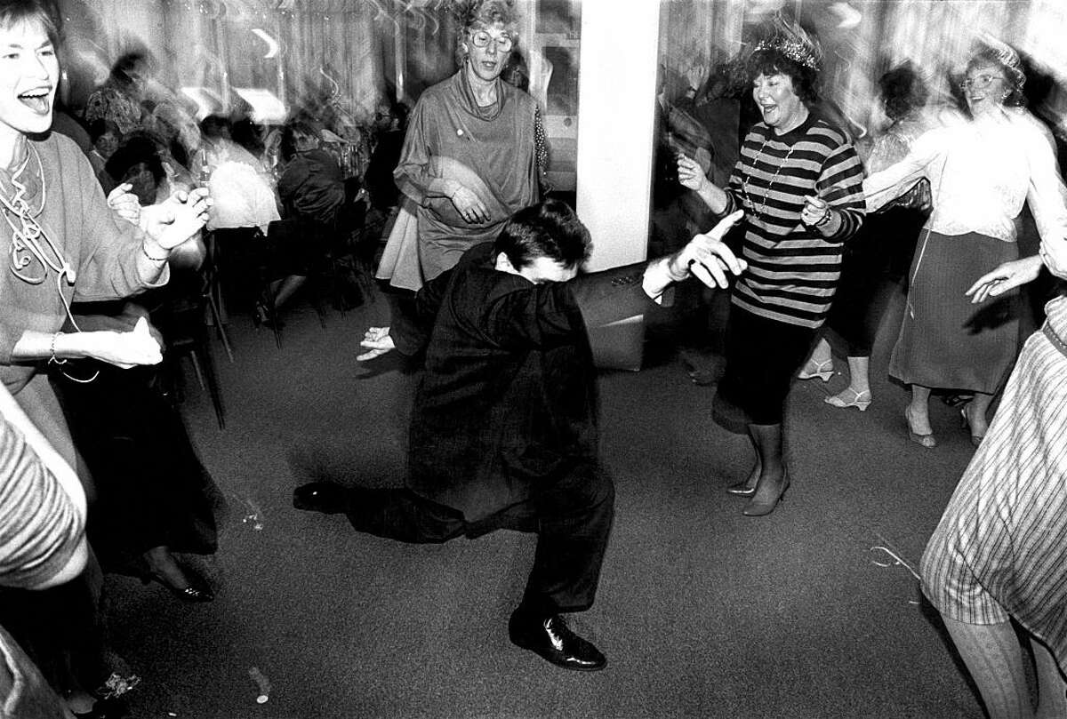 A man strikes a pose dancing in the middle of a group of older women at an office Christmas party in Newport, Wales, around 1990.