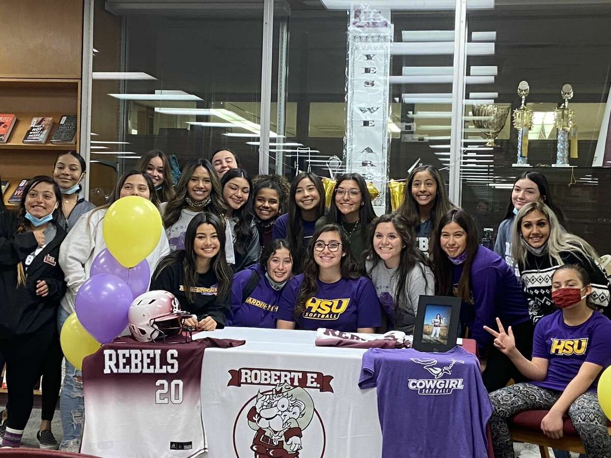 Lee softball player ChasityTrevino, middle, is surrounded by her teammates as they celebrate her signing a letter-of-intent with Hardin-SimmonsThursday.