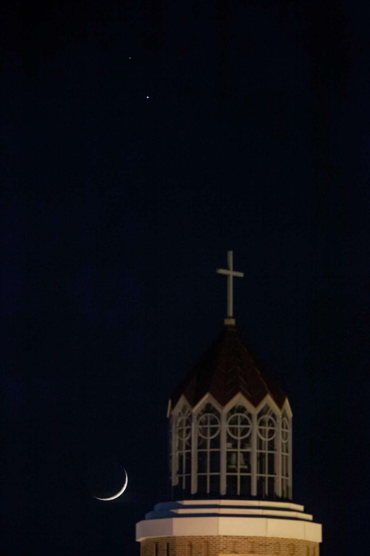 The moon sets behind the steeple of Our Lady of Lourdes Catholic Church, Wednesday night, Dec. 16, 2020, in Columbia, Mo. At upper left is Saturn and just below it and to the right is Jupiter. The three are the closest they will be, but on the evening of Dec. 21, Saturn and Jupiter's conjunction will be the closest in 800 years, prompting some to call their combined brightness the Christmas Star.