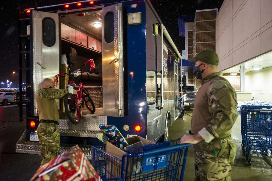 Midland police officers Mike Bess, left, and Jeremy Davis, right, load toys donated by Meijer into a SWAT vehicle before transporting them to families at the Salvation Army Midland Corps Community Center as part of the annual Shop with a Hero event, which was adapted this year due to the COVID-19 pandemic, Thursday, Dec. 17, 2020 in Midland. (Katy Kildee/kkildee@mdn.net) Photo: (Katy Kildee/kkildee@mdn.net)
