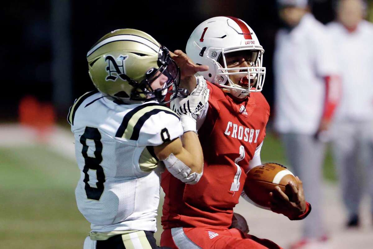 Crosby quarterback Reggie Branch (1) pushes off Nederland's Kyndon Fuselier (8) during the first half of a high school football game at Cougar Stadium Friday, Dec. 4, 2020 in Crosby, TX.