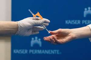 Kaiser Nurse Scott Keech (left) receives a needle from another employee to administer one of the first ten Pfizer COVID-19 coronavirus vaccines to frontline workers at Kaiser San Francisco hospital on December 17, 2020.