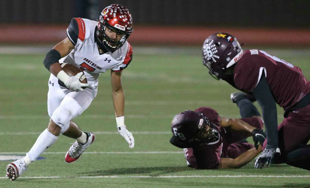 Caleb Camarillo stays low on a pivot around Hornet defenders as Southside plays Flour Bluff in high school football playoffs at Alamo Stadium on Dec. 17, 2020.