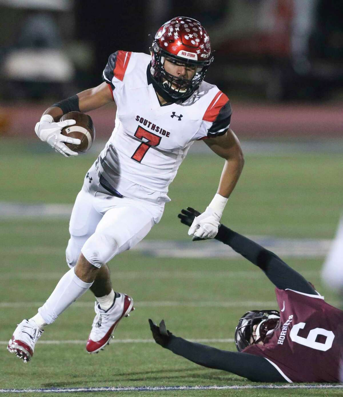 Caleb Camarillo leaves atackler reaching as he gets away as Southside plays Flour Bluff in high school football playoffs at Alamo Stadium on Dec. 17, 2020.