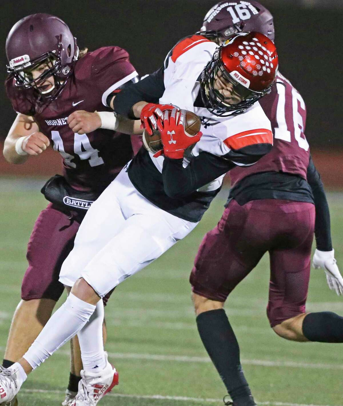 Cardinal Senobio Ortiz gets away with a catch between two clashing defenders when Southside faces Flour Bluff in the high school playoffs at Alamo Stadium on December 17, 2020.