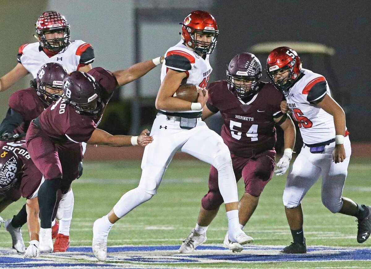 Cardinal quarterback Richard Torres surprises the defense with a run in the middle as Southside plays Flour Bluff in the high school playoffs at Alamo Stadium on December 17, 2020.