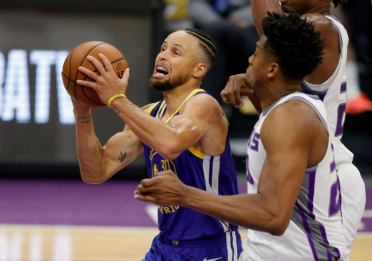 SACRAMENTO, CALIFORNIA - DECEMBER 17: Stephen Curry #30 of the Golden State Warriors goes up for a shot on Hassan Whiteside #20 at Golden 1 Center on December 17, 2020 in Sacramento, California. NOTE TO USER: User expressly acknowledges and agrees that, by downloading and or using this photograph, User is consenting to the terms and conditions of the Getty Images License Agreement. (Photo by Ezra Shaw/Getty Images)