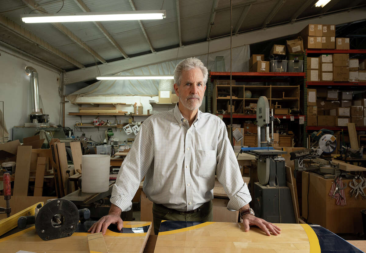 Ward Wallau stands behind his current project, a custom desk crafted from authentic Cal Basketball flooring from Haas Pavilion.