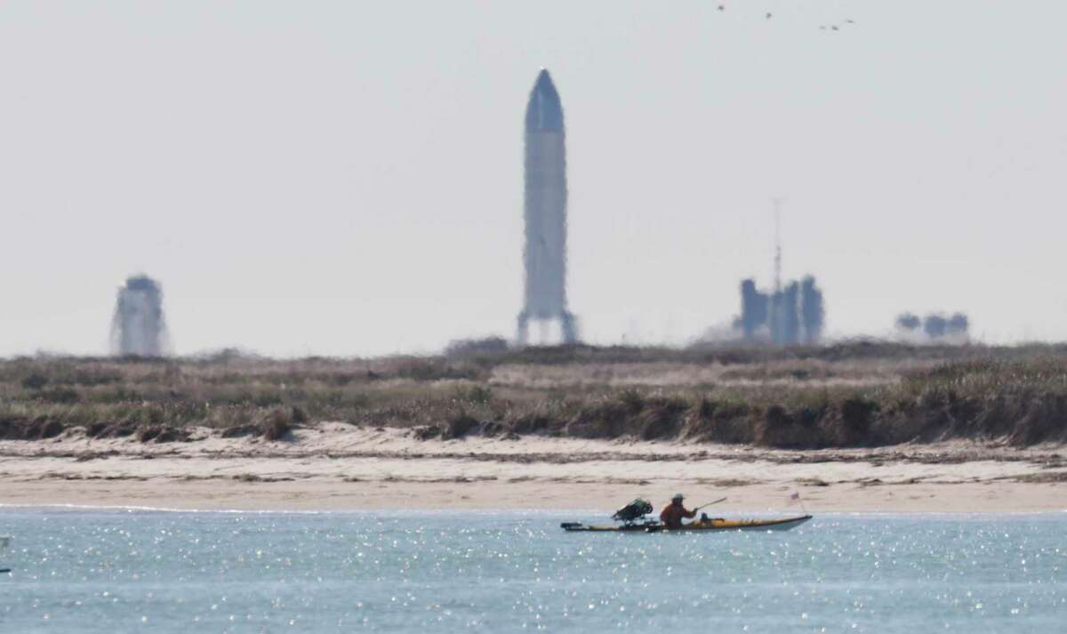 A kayaker is seen from Isla Blanca Park on South Padre Island. Many space enthusiasts from all over the country converged on the Texas beach town where just around 5 miles away stands SpaceX's Starship SN8, seen on the horizon before its Dec. 9 launch.