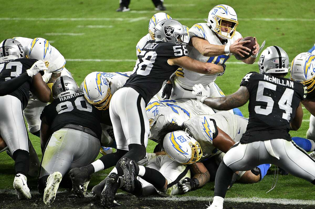 Chargers quarterback Justin Herbert reaches for the end zone on the last play of Los Angeles' overtime victory against Las Vegas, which had taken the lead with a Daniel Carson field goal earlier in extra time.