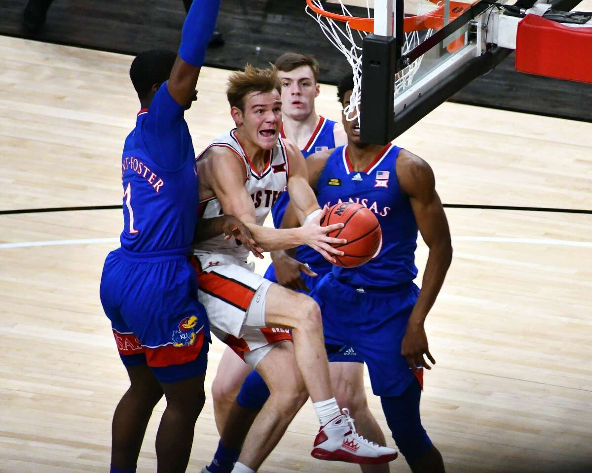 Texas Tech's Mac Clung splits between a trio of Kansas defenders during their Big 12 conference men's basketball game on Dec. 17, 2020 in the United Supermarkets Arena in Lubbock.