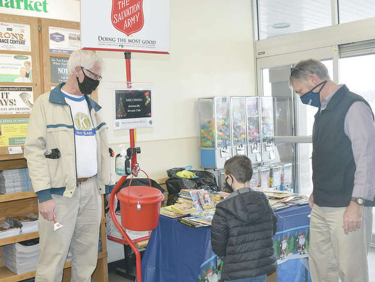 Kiwanis Club of Jacksonville members Gary Grams and Gary Scott, volunteer bell ringers for The Salvation Army, help a child pick out a book on Thursday at County Market in Jacksonville. The Kiwanians were giving out the books free as part of a club initiative.