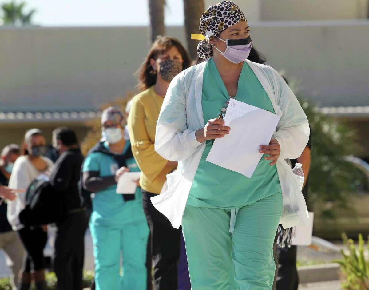 Health care personnel line up outside the Edinburg Conference Center to receive the COVID-19 vaccine on Thursday, Dec.17,2020 in Edinburg, Texas. (Delcia Lopez/The Monitor via AP)