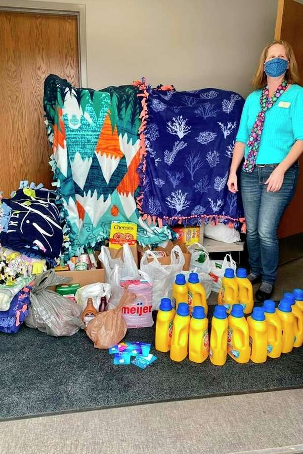 Women's Issues Chair Nancy Pnacek stands beside the donations given to Shelterhouse by the John Alden Chapter,Daughters of the American Revolution. (Photo provided)