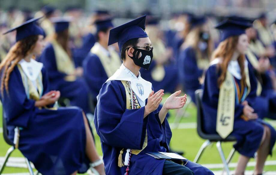 Valedictorian Shaw-Sean Yang, center, claps during a graduation ceremony for Lake Creek High School at MISD Stadium, Thursday, June 4, 2020, in Montgomery. The 220 students in the school's inaugural graduating class attended the outdoor ceremony with social distancing and other safety guidelines. The Montgomery Independent School District is moving forward with the Class of 2021's indoor graduation plans as the coronavirus pandemic continues. Photo: Jason Fochtman, Houston Chronicle / Staff Photographer / 2020 © Houston Chronicle