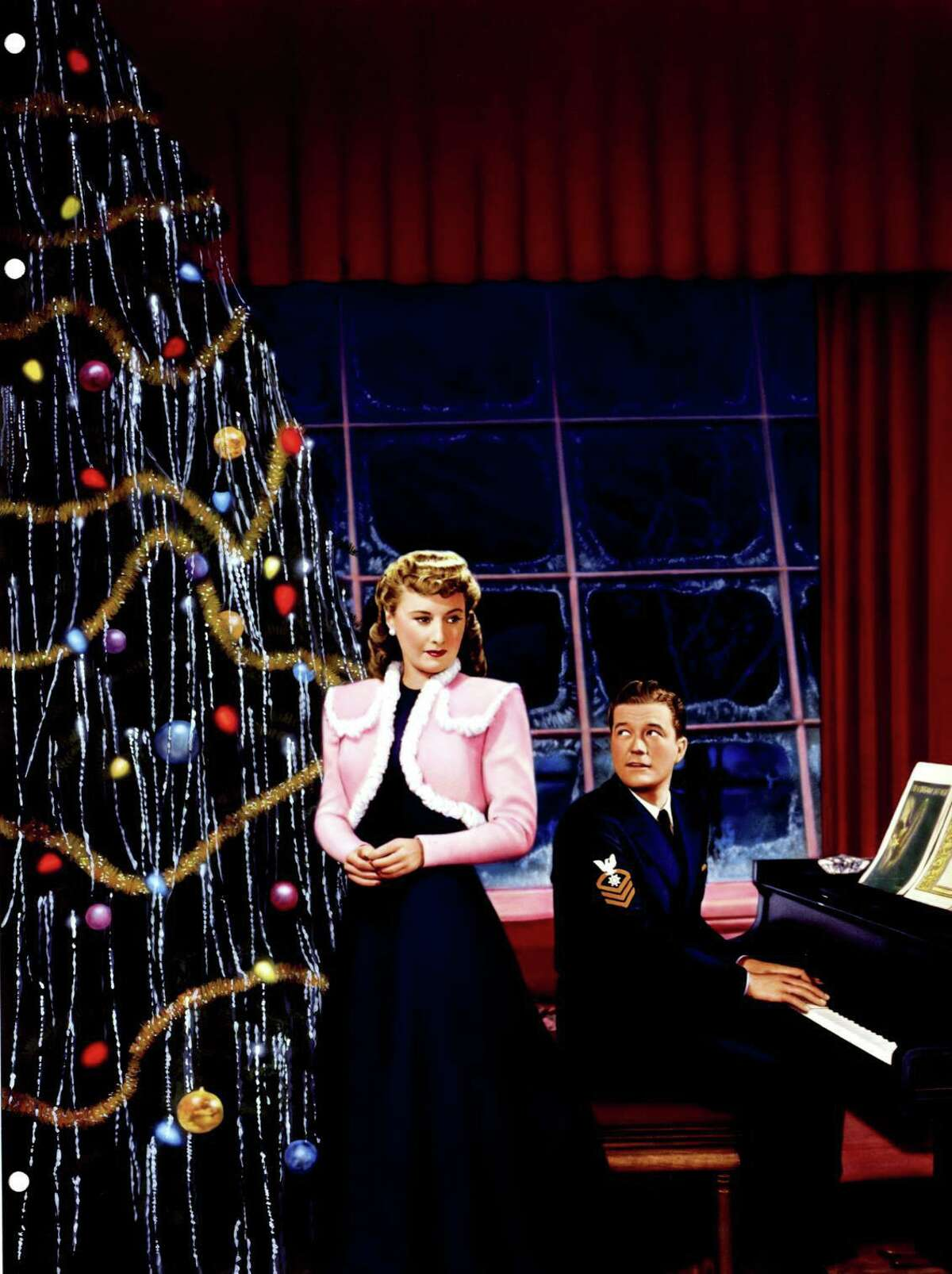 """Barbara Stanwyck and Dennis Morgan are seen in a poster for 1945's """"Christmas in Connecticut."""" Elizabeth, who is single, portrays herself as a Connecticut farm wife who's a whiz in the kitchen. All is well until her pushy publisher forces her to host a fan of her column, a returning war hero, at her home for the holidays. Her job on the line, she pretends to be everything she's not, using a suitor's farmhouse as her base. (The suitor, an architect, claims to love her but she's told him it's not mutual.) When handsome Navy hero Jefferson Jones (actor Dennis Morgan) shows up, she falls for him. With a name like """"Christmas in Connecticut,"""" you might think this movie, or at least parts, were filmed here. Not true. The farmhouse wasn't even real. It was a set built on a Warner Bros. soundstage in Burbank, Calif., said Julia Sweeten, whose popular blog, """"Hooked on Houses,"""" shares her obsession with memorable movie and TV houses, celebrity houses and HGTV. """"Besides the fabulous Barbara Stanwyck and her amazing wardrobe in the movie, the primary draw for me was the setting,"""" she said, of the house, with a grand fireplace so tall, the mantel is over the heads of the people. When she researched the movie for her blog, she was intrigued by the Taber link."""