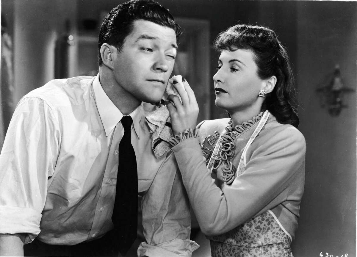 American actor Barbara Stanwyck uses a washcloth to dab Dennis Morgan's face in a still from the film,