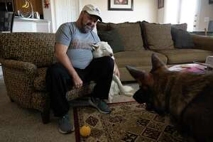 Ivy Jay Arroyo plays with his dogs Odin, left, and Bear, right, at his home in Pflugerville on Nov. 2. He spent weeks hospitalized and on a ventilator at Baylor Scott & White Hospital in Temple with COVID-19. Arroyo was transferred by ambulance after his discharge to a rehab facility in Round Rock. While the hospitals were in-network with his insurance, the ambulance was not. He was stuck with a $2,200 bill that was sent to collections.