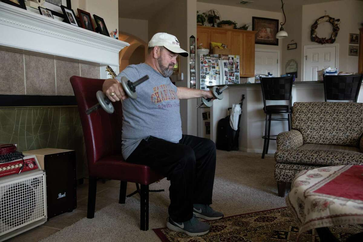 Ivy Jay Arroyo performs strength training exercises at his home in Pflugerville in November. Since his battle with COVID-19, Arroyo has lost weight and muscle mass and has neurological issues with his sense of balance.