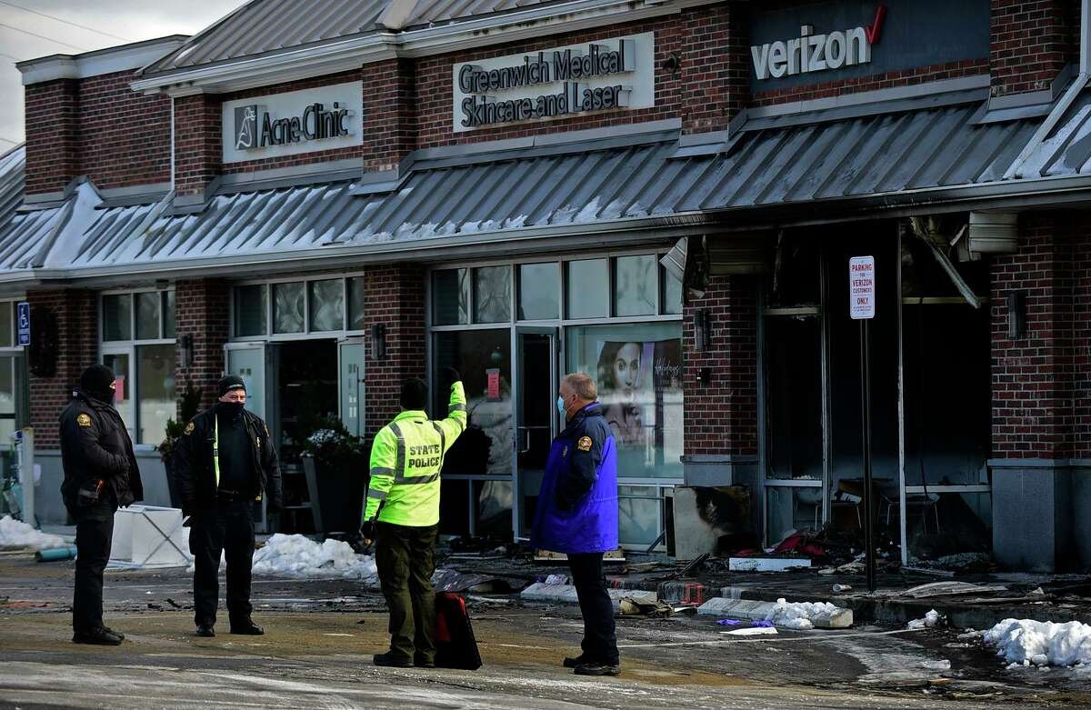 Police investigate the fire at the Verizon store on Putnam Ave Friday, December 18, 2020, in Greenwich, Conn.
