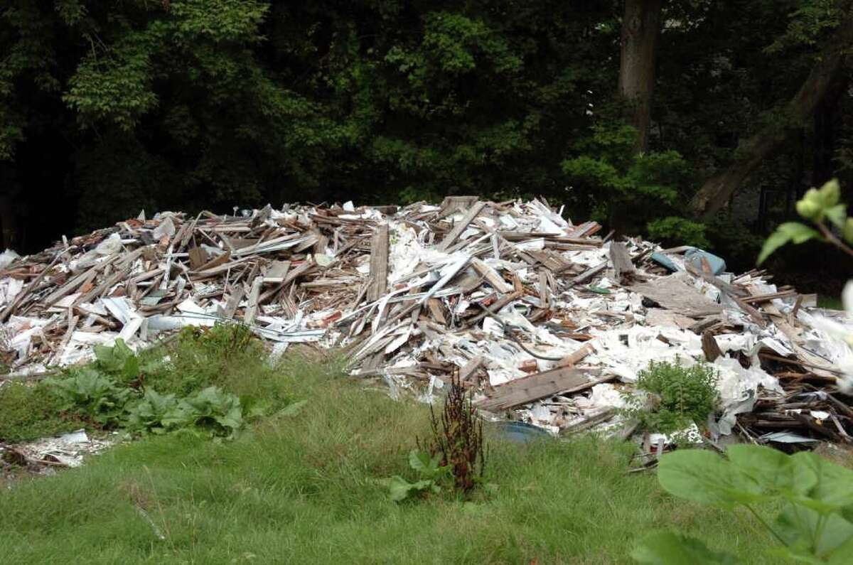 A pile of rubble sits where a house once stood at 161 North Oak Avenue in Shelton. The structure was torn down following a mudslide on the cliff at the end of the street.