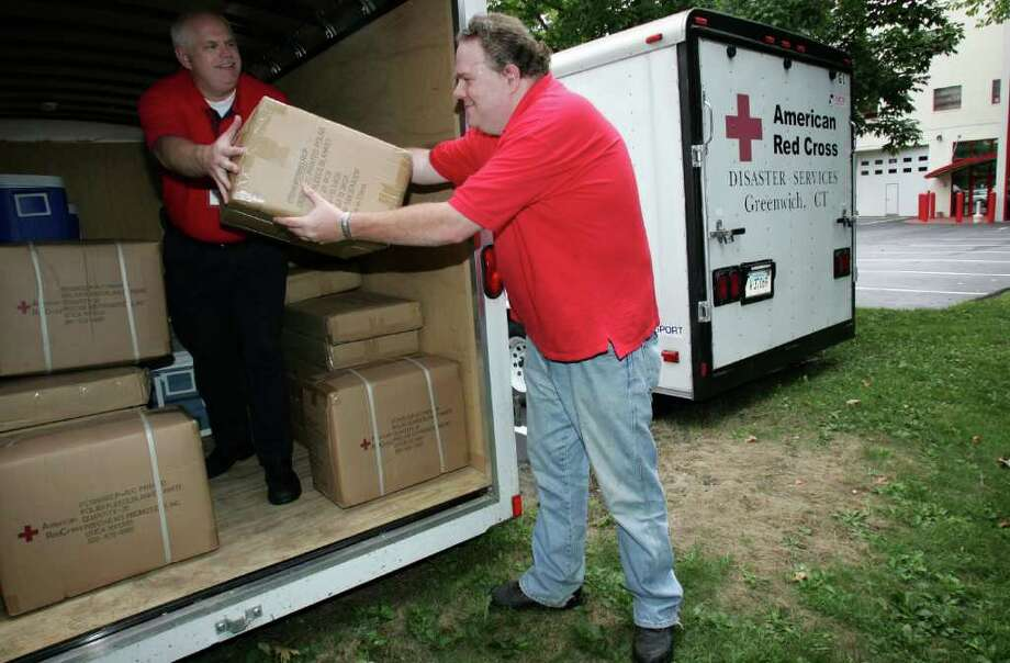 Greenwich Red Cross Director of Emergency Services Tim Wall, left, and chapter volunteer Bill Augustine load a trailer Friday afternoon with enough supplies for 200 people in preparation for Hurricane Earl. Photo: David Ames, David Ames/For Greenwich Time / Greenwich Time Freelance