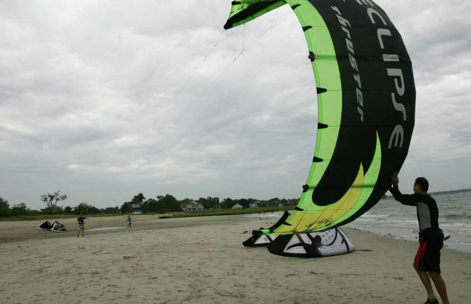 Kite boarder Ervin Braun, right, helps Doran Welch get his kite airborne at Greenwich Point Friday afternoon during the high winds produced by Hurricane Earl. Photo: David Ames, David Ames/For Greenwich Time / Greenwich Time Freelance