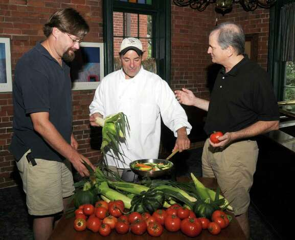 Two Steps Grille owners, Keith O'Marra, center, and Tom Devine, right, discuss the fresh produce to be used at the upcoming Harvest Dinner at Tarrywile Mansion, with Jeremy Schulz, left, of Clatter Valley Farm, in New MIlford, on Friday September 3, 2010.  Schulz's farm will be providing the produce for the dinner. Photo: Jay Weir / The News-Times Freelance