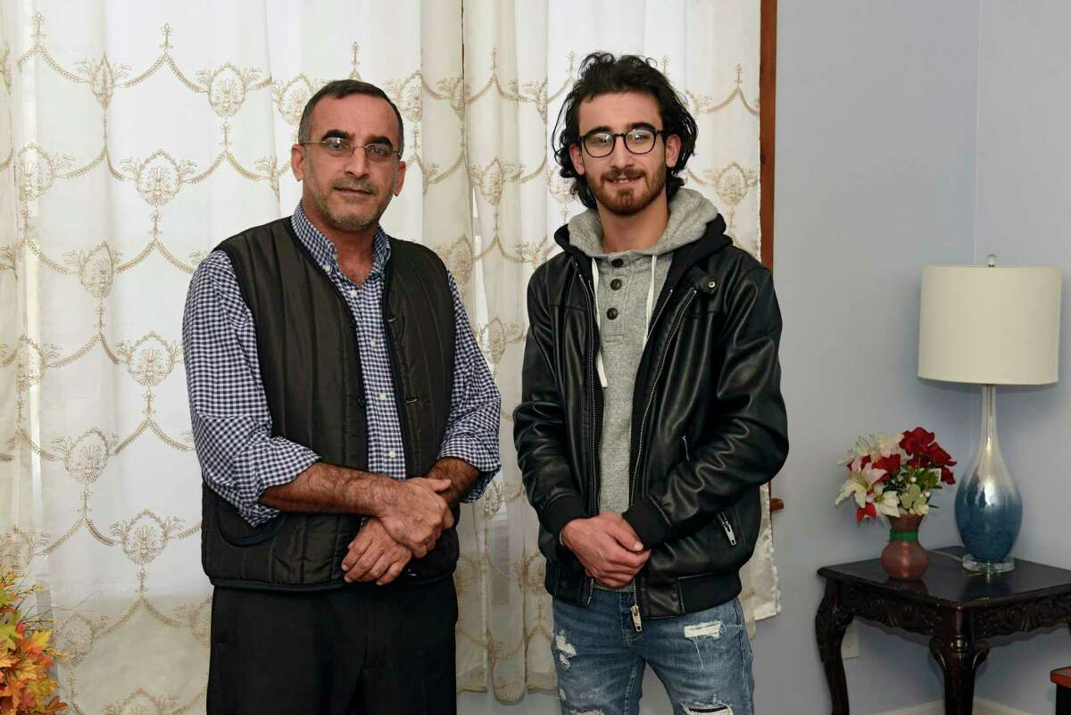 Ibrahim Alkahraman, left, stands with his son Khalil in their home on Thursday, Dec. 17, 2020 in Albany, N.Y. (Lori Van Buren/Times Union)