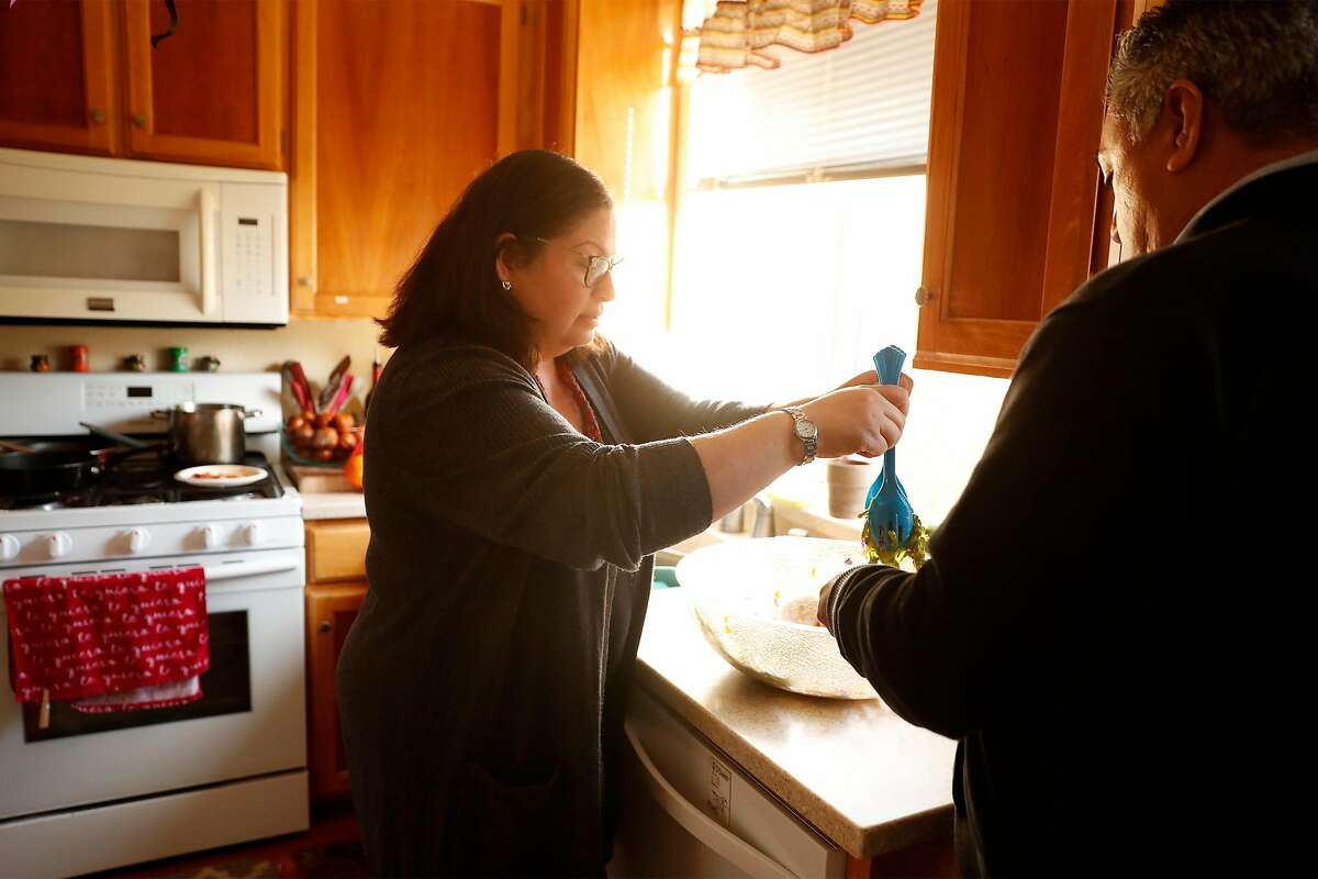 Verónica Hernández, serves lunch to her husband, Juan, at their home in Santa Rosa, Calif., on Thursday, December 17, 2020. Hernández' uncle, José Jesús Arroyo, lost his life to COVID-19 earlier this month.