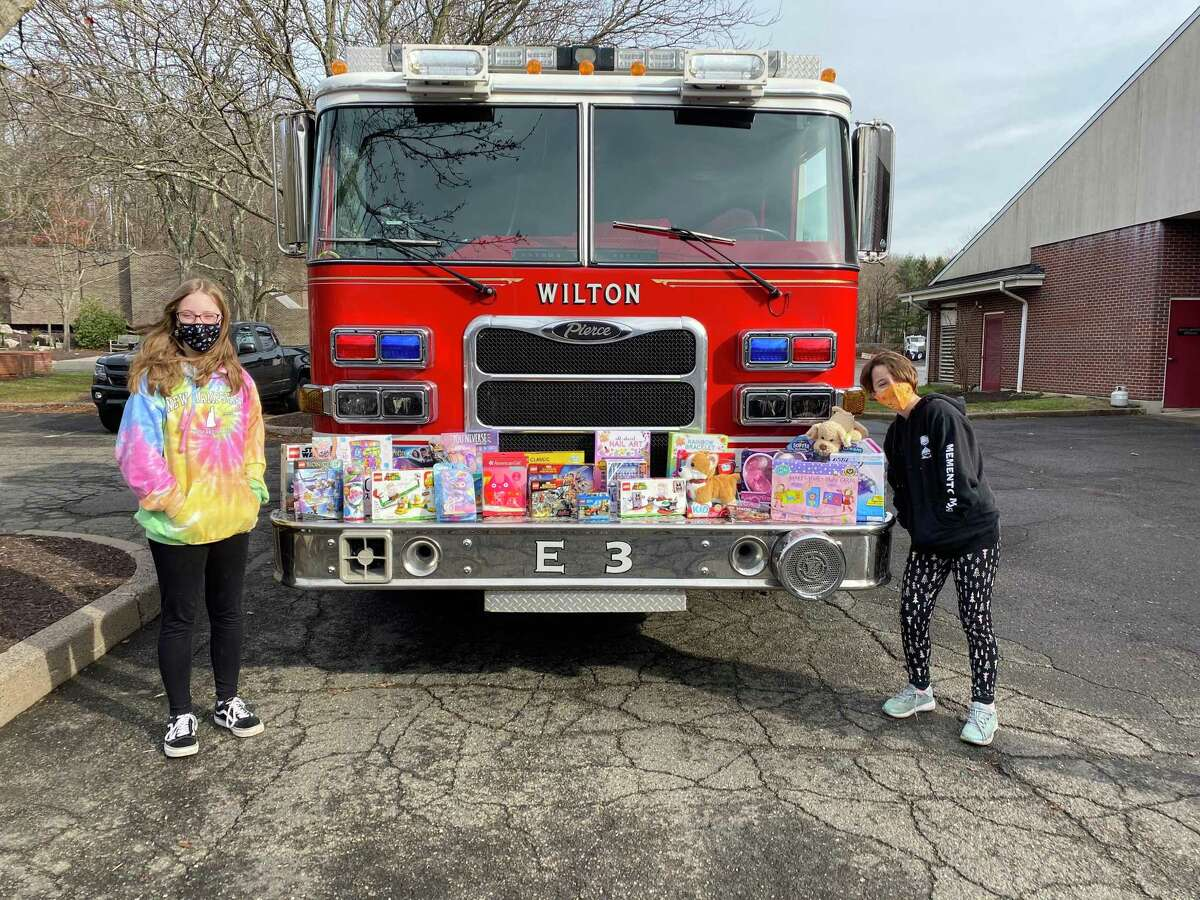 Troop #50798 Cadettes Lucy, left, and Annabelle Shultz with the collection of toy donations dropped off Dec. 13, at the Wilton Fire Department.