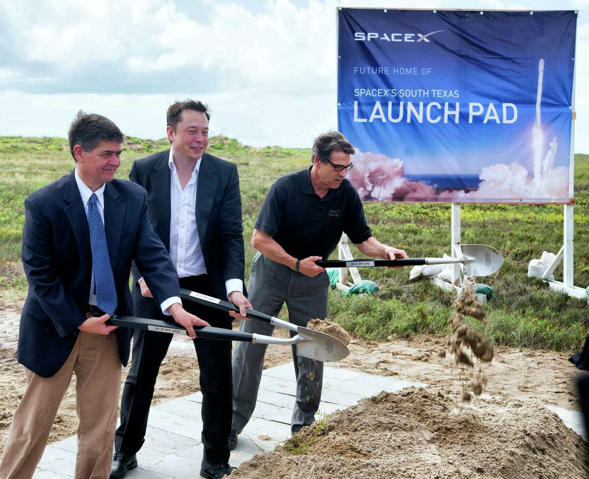 In a Sept. 22, 2014 file photo, U.S. Rep. Filemon Vela, left, SpaceX founder and CEO Elon Musk, center, and Texas Gov. Rick Perry turn the first shovel-full of sand at the groundbreaking ceremony for the SpaceX launch pad at Boca Chica Beach, Texas. Musk recently moved to Texas from California.