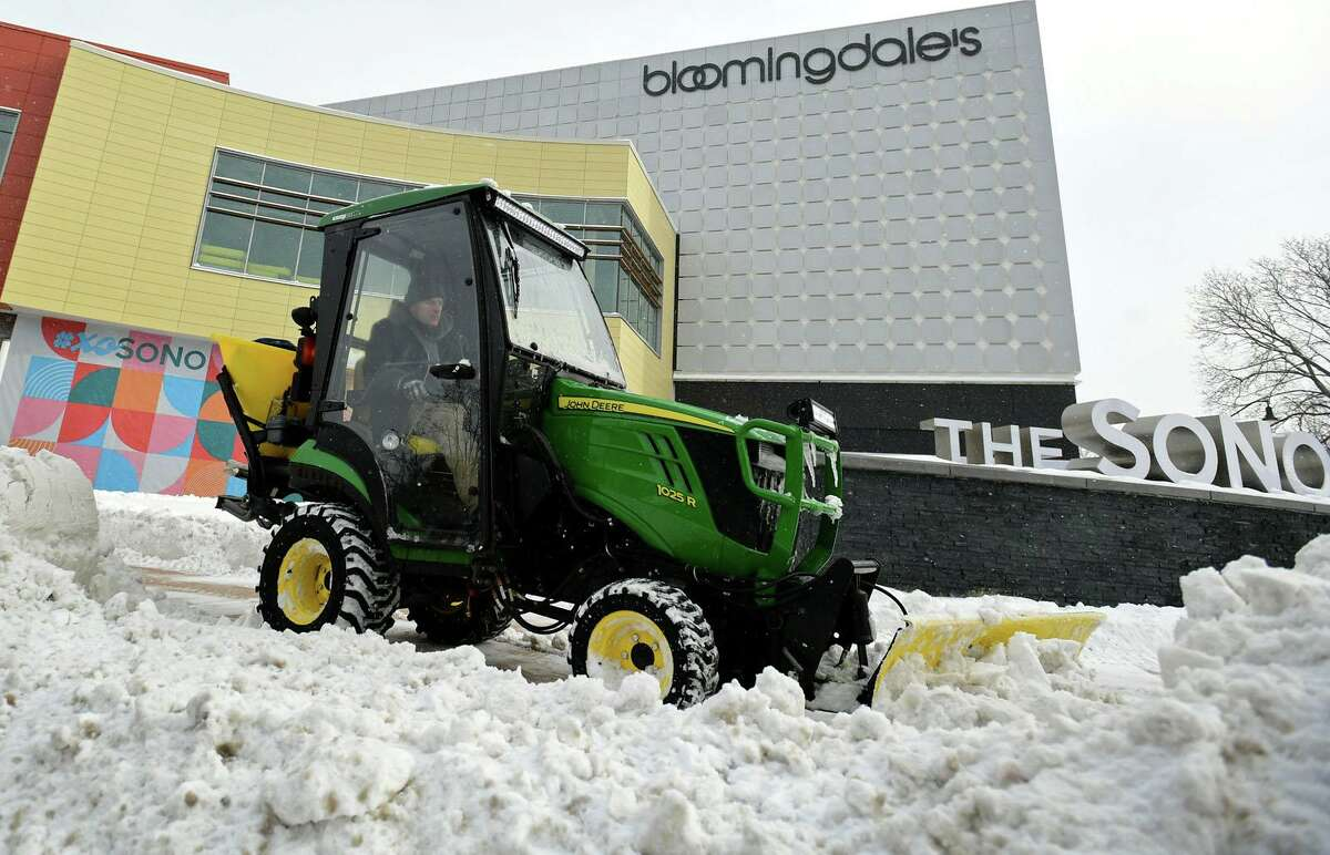 A mantainence worker plows the sidewalk in front of the SoNo Collection mall following the snowstorm Thursday, December 17, 2020, in Norwalk, Conn.