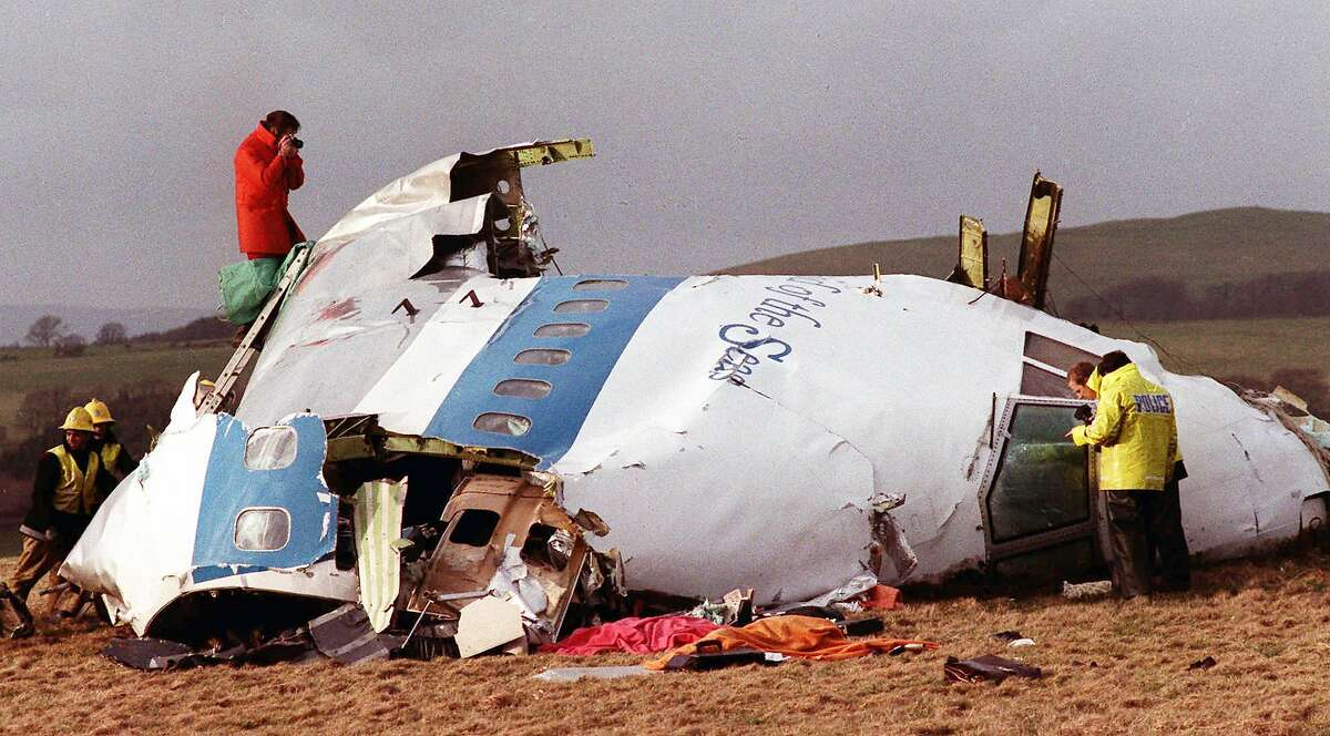 FILE - This Dec. 22, 1988 file photo shows Police and investigators look at what remains of the flight deck of Pan Am 103 on a field in Lockerbie, Scotland. Moammar Gadhafi's death on Oct. 20, 2011, resonates with the families who had loved ones on the airliner who held Gadhafi responsible for sanctioning the 1988 bombing that killed 270 people. (AP Photo/File)