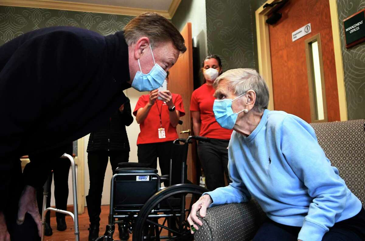 Gov. Ned Lamont greets Jeanne Peters, 95, a rehab patient at The Reservoir, a nursing facility in West Hartford, after she was given the first COVID-19 vaccination at the nursing home Friday, Dec. 18, 2020. The home, owned by Genesis HealthCare, is among those where a strike has been authorized.