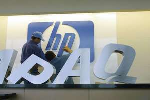 Electricians change the Compaq Computer sign at the company's campus in Houston, Saturday, May 4, 2002. After one of the harshest and closest proxy fights in American business history, Hewlett-Packard Co. officially closed its $19 billion acquisition of Compaq Computer Corp. on Friday. (AP Photo/Michael Stravato)