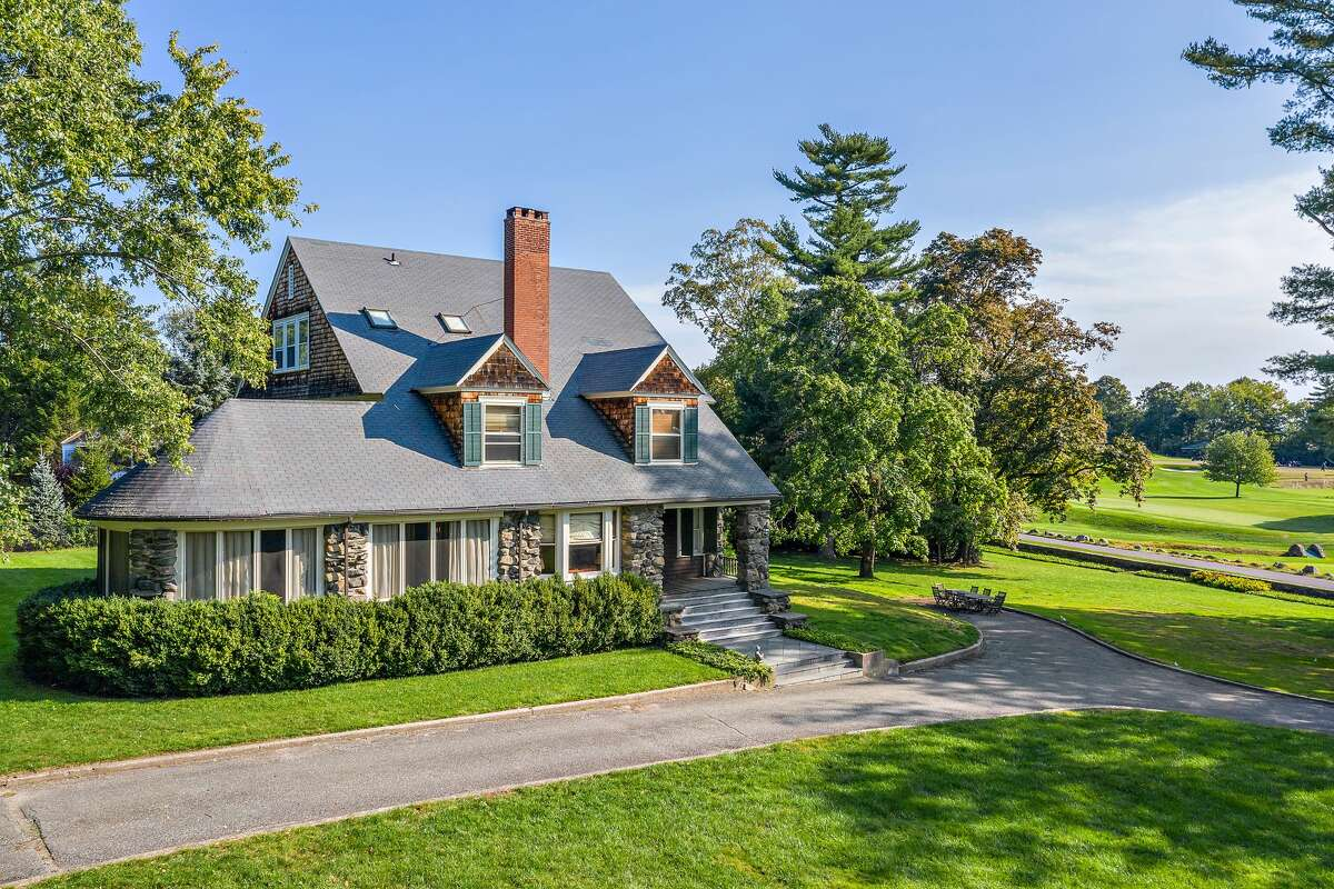"""Colonial house looking over the Greenwich Country Club'€™s scenic golf course at 3 Fairfield Road in Greenwich. """"(It) marries yesterday's timeless charm with modern conveniences,"""" said Jack Sarsen, its listing agent. """"The interior has been gut renovated to meet today's standards with high ceilings, great flow and an open-concept kitchen with stainless steel appliances and an adjacent family room."""" The rustically elegant appearance of the exterior gives way to a sophisticated color scheme within the 5,690 square feet of living space, where creative painting techniques and cool colors are found on some walls and even on some ceilings and one floor."""