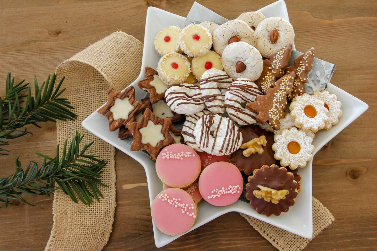 Homemade selection of christmas cookies on a star shaped plate. Cookies include shortcrust pastry cookies, chocolate cookies, cinnamon star cookies and many more.