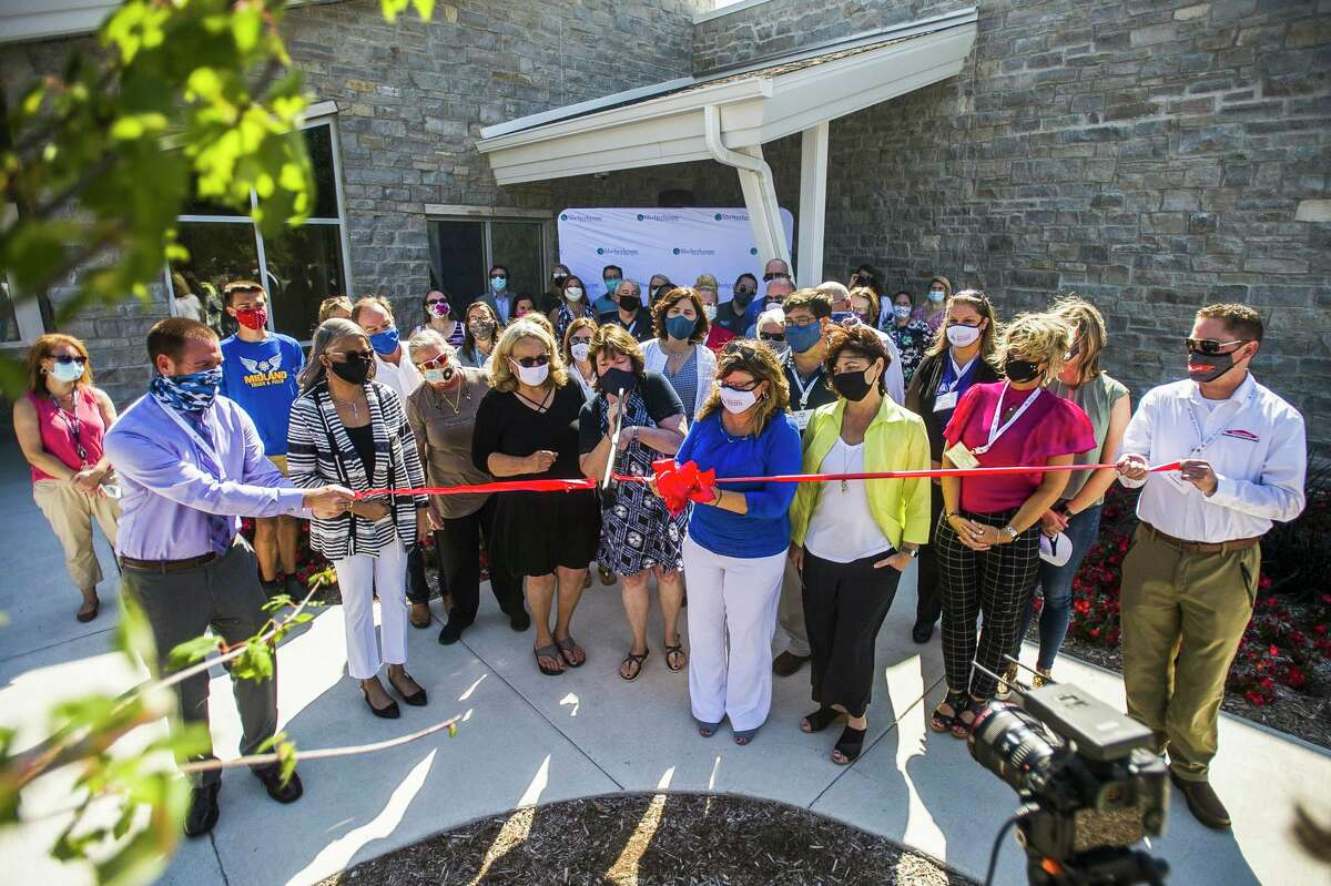 Members of the Midland Business Alliance, Shelterhouse staff and benefactors attend a ribbon cutting ceremony at Shelterhouse's new facility at 2500 Waldo Rd. Thursday, Aug. 20, 2020 in Midland. (Katy Kildee/kkildee@mdn.net)