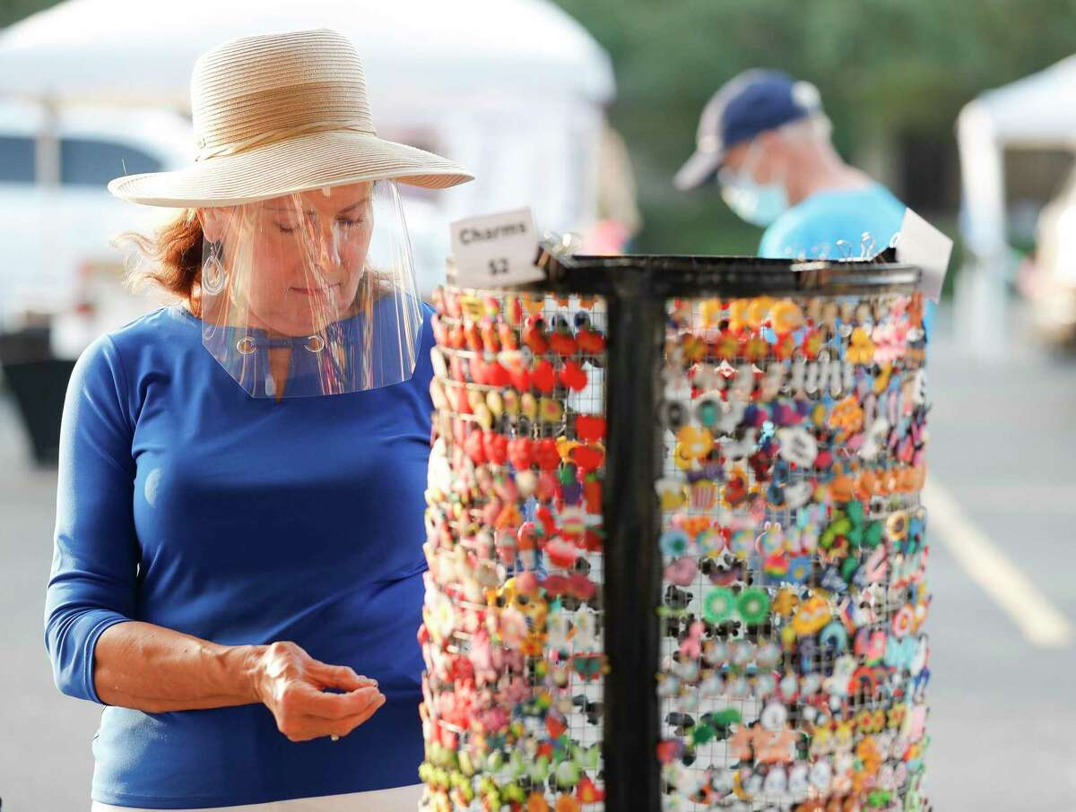 Barbara Setchfield wears a face shield as she looks over a series of charms used to decorate it during The Woodlands Farmers Market, Saturday, Sept. 19, 2020, in The Woodlands. The market's organizers OK'd a series of changes for 2021, including tweaked hours - from 9 a.m. to 1 p.m. - adding 'cottage' vendors and the sale of CBD products.