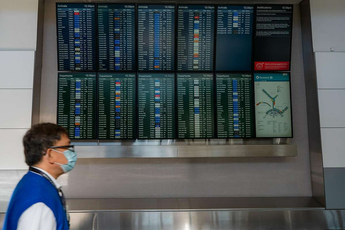 An airport employee walks past arrival and departure screens at San Francisco International Airport on Friday, December 18, 2020.