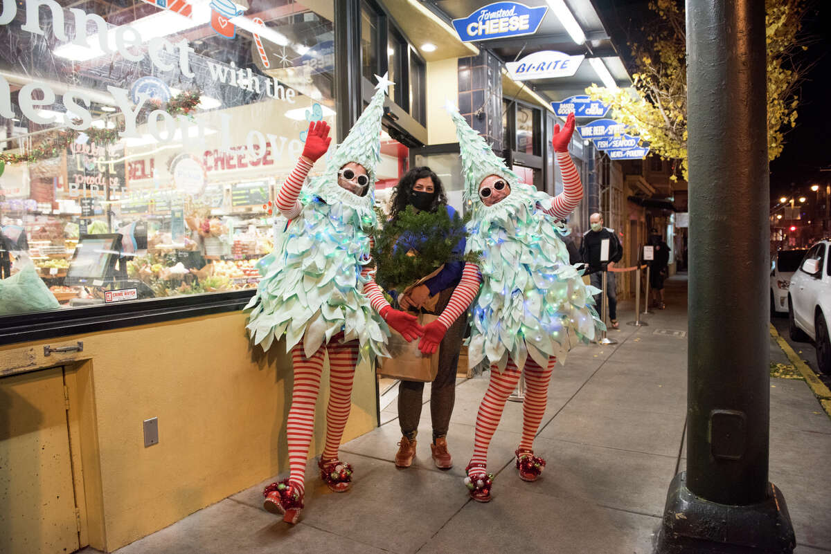 Tree #1 and Tree #2, aka the Tree Twins pose with bi-rite shopper, Leah Speert.