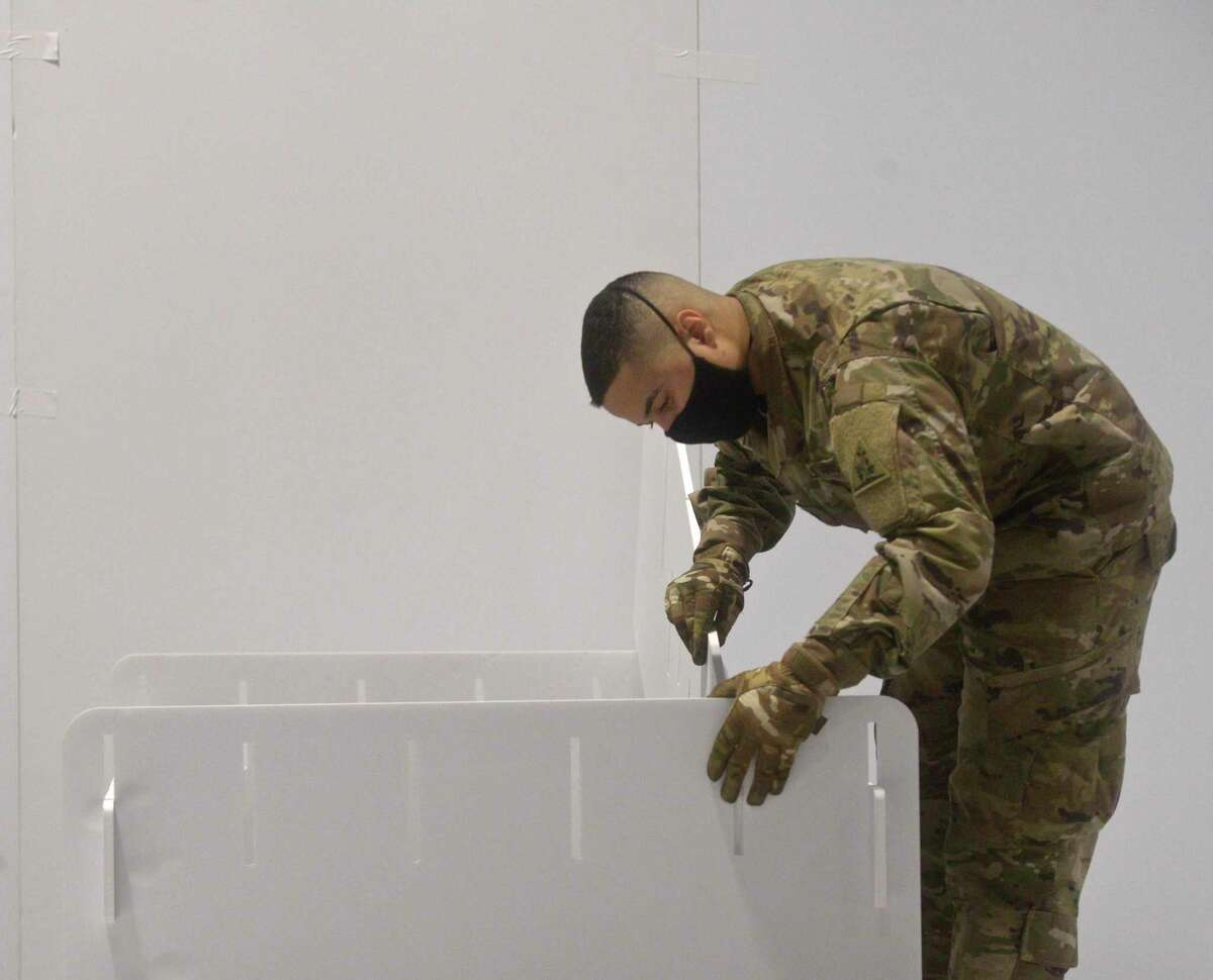 Spc Marcos Cotto, of Hartford, assembles a bed at the Connecticut Convention Center on Friday. The Connecticut National Guard set up a field hospital in the conventen center. Hartford HealthCare will be operating the site, December 18, 2020, in Hartford, Conn.