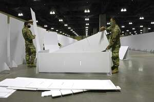 Pvt. Carter Ouellette, of Trumbull, left, and Spc Jonathan Kang, of Rocky Hill, assemble a bed at the Connecticut Convention Center on Friday. The Connecticut National Guard set up a field hospital in the conventen center. Hartford HealthCare will be operating the site, December 18, 2020, in Hartford, Conn.