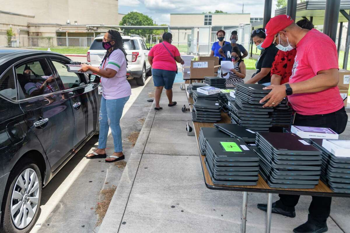 Abraham Lincoln Middle School staff members work together to pass out needed equipment for the new school year to sixth-grade parents lined up behind the school on Friday afternoon. PAISD has begun distributing books and electronic devices to students at specific times at each school. Photo made on August 14, 2020. Fran Ruchalski/The Enterprise