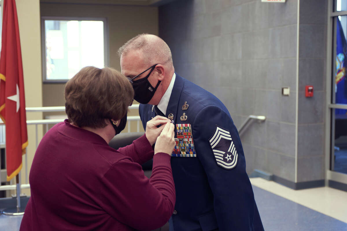 Joan Peno puts a retirement pin on her husband Chief Master Sgt. Shawn Peno's uniform.