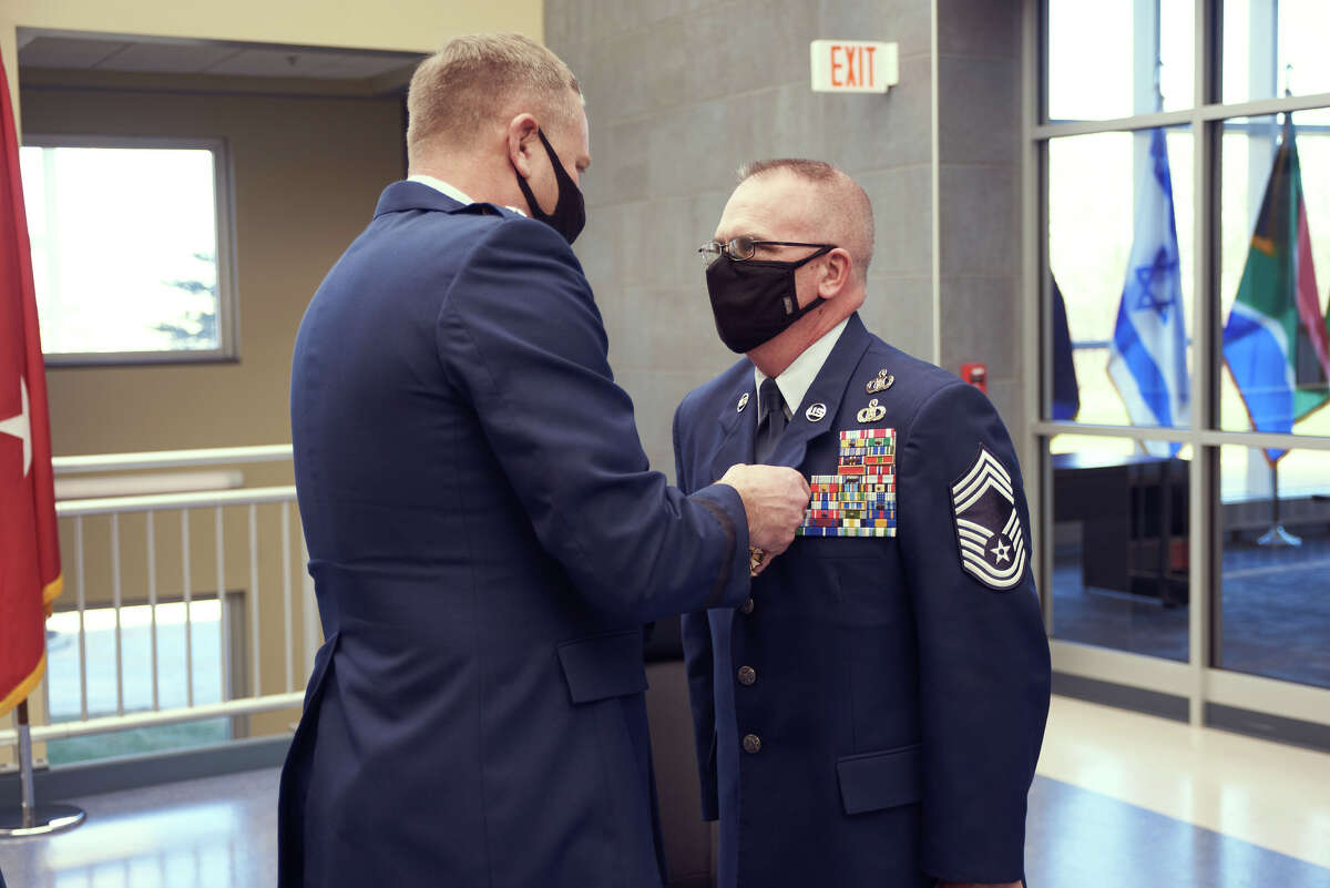 Maj. Gen. Anthony LaBarge, commander of the New York Air National Guard, presents the Legion of Merit to Chief Master Sgt. Shawn Peno during a ceremony in Latham.