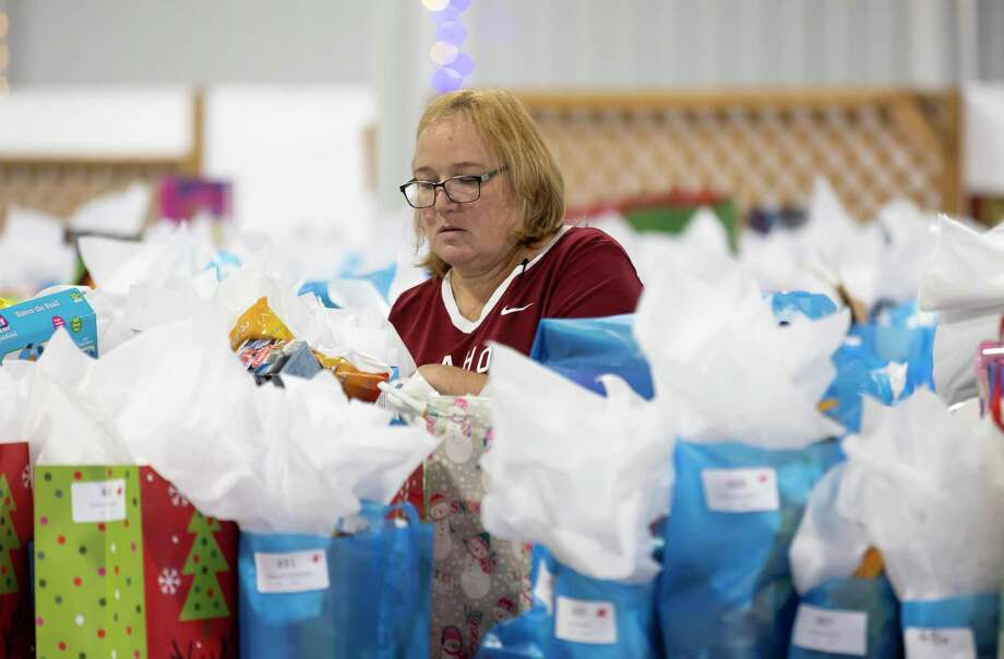Any Bryers, an alumni of the Citizens Police Academy, adds the final touches to gifts for this year's annual Operation Blue Elf in Conroe. This year's event will take place in a drive-thru style event due to the COVID-19 pandemic. Photo: Gustavo Huerta, Houston Chronicle / Staff Photographer / 2020 © Houston Chronicle